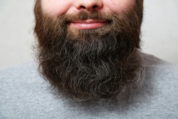 Portrait. The man with the thick beard smiles. The bearded man laughs. Lips, nose, mouth of a bearded man, close-up. A well-groomed, thick, beautiful beard. Close-up.