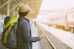 portrait the tourist young man traveler with backpack and hat Stand looking,look at the train While waiting he use the phone to check the schedule to leave travel at the train station.Travel concept.