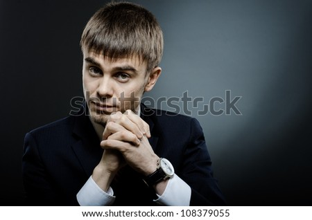 portrait  the  young businessman  in costume , fixed look, on dark blue background
