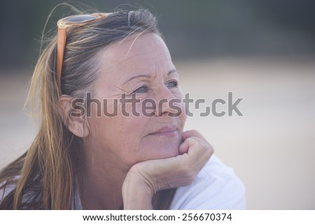 Portrait thoughtful attractive senior woman, laid back and relaxed chin on hand, peaceful confident outdoor, blurred background and copy space.