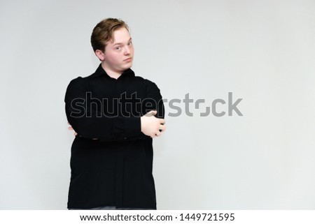 Portrait to the waist on a white background of a handsome young man in a black shirt. stands directly in front of the camera in different poses, talking, showing emotions, showing hands.