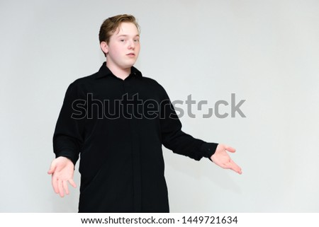 Portrait to the waist on a white background of a handsome young man in a black shirt. stands directly in front of the camera in different poses, talking, showing emotions, showing hands. #1449721634