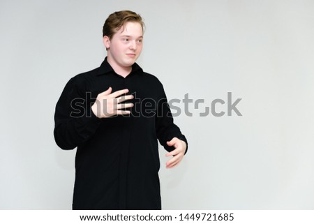 Portrait to the waist on a white background of a handsome young man in a black shirt. stands directly in front of the camera in different poses, talking, showing emotions, showing hands. #1449721685