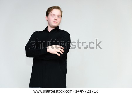 Portrait to the waist on a white background of a handsome young man in a black shirt. stands directly in front of the camera in different poses, talking, showing emotions, showing hands. #1449721718