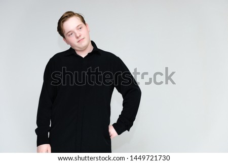 Portrait to the waist on a white background of a handsome young man in a black shirt. stands directly in front of the camera in different poses, talking, showing emotions, showing hands. #1449721730