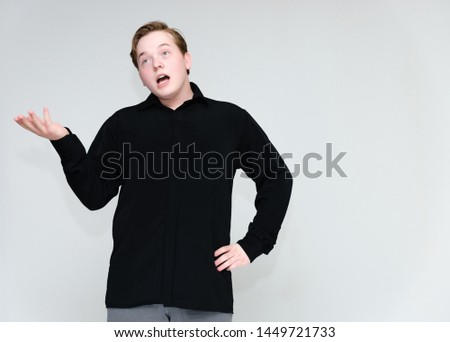 Portrait to the waist on a white background of a handsome young man in a black shirt. stands directly in front of the camera in different poses, talking, showing emotions, showing hands. #1449721733