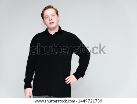 Portrait to the waist on a white background of a handsome young man in a black shirt. stands directly in front of the camera in different poses, talking, showing emotions, showing hands. #1449721739