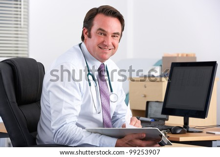 Portrait UK doctor sitting at desk