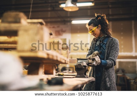 Portrait view of satisfied smiling middle aged professional female carpentry worker with steel vise on the table in the workshop.