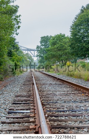 Portrait View of Train Railroad curving right, with bridge in the background #722788621