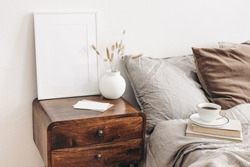Portrait white frame mockup on retro wooden bedside table. Modern white ceramic vase, dry grass. Cup of coffee and books in bed. Beige linen pillows in bedroom. Scandinavian interior.