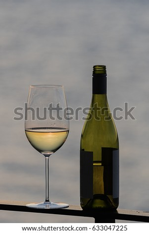 Portrait white wine with bottle on deck rail outside