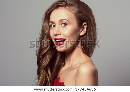 Portrait with an open mouth of a young beautiful woman romantic wavy hairstyle looks into camera. Toned image #377434636