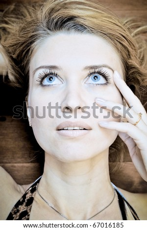Portrait with beautiful blonde girl on wooden background closeup