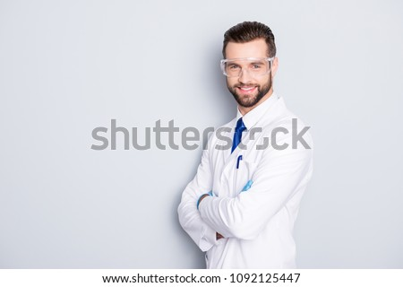 Portrait with copy space, empty place of joyful half-turned scientist with stubble in white outfit with tie having his arms crossed looking at camera isolated on grey background