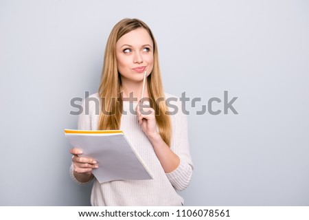 Portrait with copy space empty place of thoughtful pensive girl having copybook and pen in hands looking up, writer waiting for muse, isolated on grey background