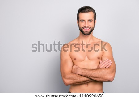Portrait with copy space of attractive, virile, harsh, sporty, manly, stunning man with crossed arms, muscular, naked torso, looking at camera, isolated on gray background