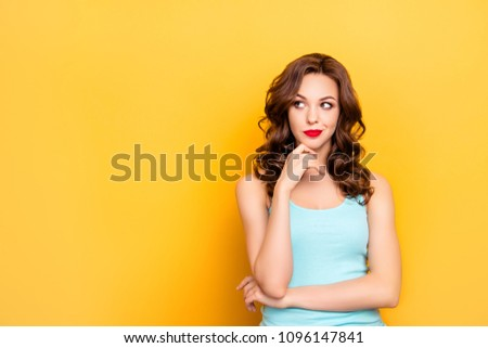 Portrait with copy space of thoughtful doubtful girl with modern hairdo looking at empty place holding hands on chin isolated on yellow background
