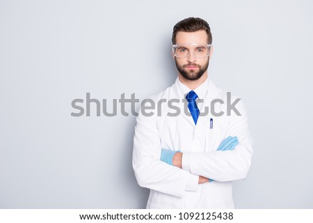 Portrait with copyspace, empty place of stylish handsome scientist with stubble in white outfit with tie having his arms crossed looking at camera isolated on grey background