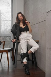 Portrait with soft light of elegant beautiful tanned caucasian woman with long straight brunette woman in black lace top and white trousers posing in loft interior wth concrete walls and big window