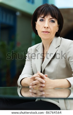 portrait woman brunette sitting glass table