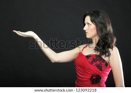 Portrait woman in red dress black background