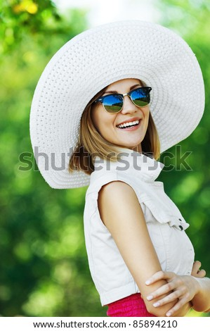 portrait woman wearing sunglasses standing white hat sideways smile