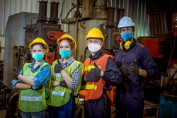 Portrait woman worker and engineer  under inspection and checking production process on factory station by wearing safety mask to protect for pollution and virus in factory.They good signal in work.