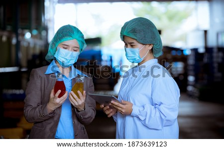 Portrait worker of science in bottle beverage factory wearing safety uniform ,face mask discussion and working to check quality of drink Basil seed produce on conveyer before distribution to market. Photo stock ©