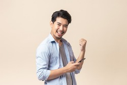 Portrait young Asian man handsome happy smile in formal shirt using smartphone trading or chatting on brown isolated studio background.
