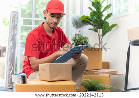 Portrait young Asian man house moving service worker in uniform doing home relocation, checking list cardboard boxes for preparing to move. Package delivery resident relocation moving service concept. Foto stock ©
