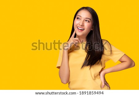 Portrait young asian woman look at copy space Beautiful girl wear yellow T shirt with yellow background at studio Pretty asia female get confident. Female get satisfied something Lovely lady get happy