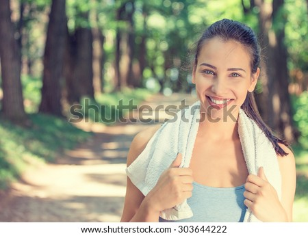 Portrait young attractive smiling fit woman with white towel resting after workout sport exercises outdoors on a background of park trees. Healthy lifestyle well being wellness happiness concept Stock foto ©