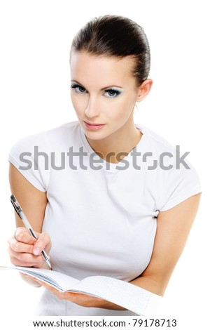 Portrait young beautiful dark-haired woman-student who writes in exercise book with pen, isolated on white background.
