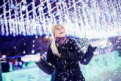 Portrait young beautiful girl rejoices to first snow and winter,, evening illumination background.