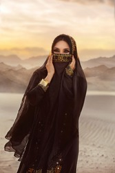 Portrait young beautiful oriental girl. face arabian woman hidden by veil black scarf. evening make-up, smoky eyes. head is covered hood hidjab. Traditional dress gold embroidery. Nature desert sunset