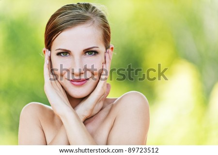 portrait young beautiful woman bare shoulders holding palm cheeks background summer green park