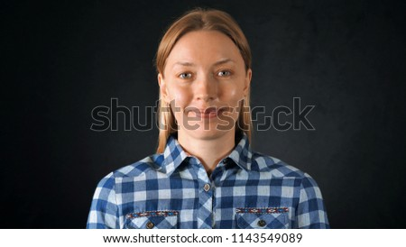 portrait young caucasian woman with blond hair posing on black background. attractive girl wearing casual bright shirt looking at the camera