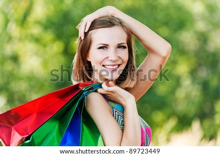 portrait young charming short-haired woman shopping bags behind background summer green park