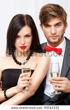 Portrait young couple with glass of champagne, wear evening dress red lips and suit with red bow, glamour vogue style, sensual looking at camera, sitting indoors