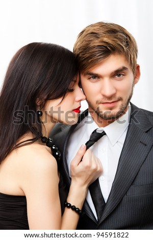 Portrait young couple, woman hold grab man tie with closed eyes, wear evening dress and suit, glamour vogue style, guy sensual looking at camera, sitting indoors