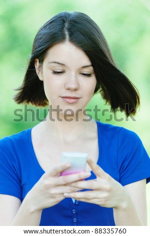 portrait young dark-haired pretty girl park holds mobile phone reads message background summer green park