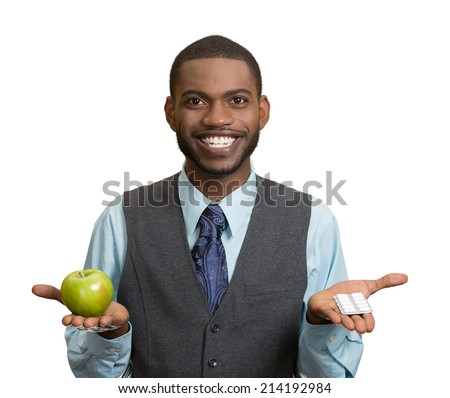 Portrait young, fit, happy handsome man holding green fresh apple in one hand, pills, vitamins in another. Sugar free chewing gum, dentist recommended. Face expressions, emotion, health care. Dieting