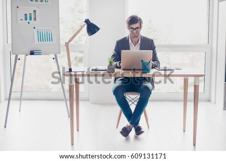 Portrait young handsome businessman with glasses is sitting at desk in workstation, smiling and typing on laptop.