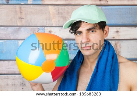 Portrait young handsome man in front of wooden blue vintage background with ball and cap