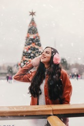 Portrait young happy attractive woman in stylish jacket wear pink earmuffs and mittens on ice rink. Cheerful beautiful girl have fun on open skating rink. Woman skating ice rink. Winter entertainment
