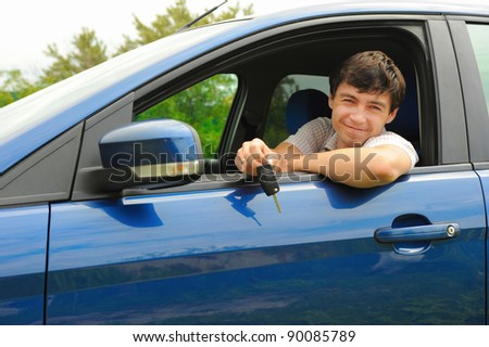 portrait young happy man showing the keys sitting in new car