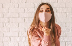 Portrait young happy millennial woman in trendy medical face mask blowing air kiss with hand. Beautiful stylish hipster girl in pink protective mask send blow kiss. Girl gesture blow kiss in face mask