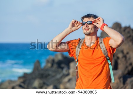 portrait young man in glasses with backpack. Backround sea