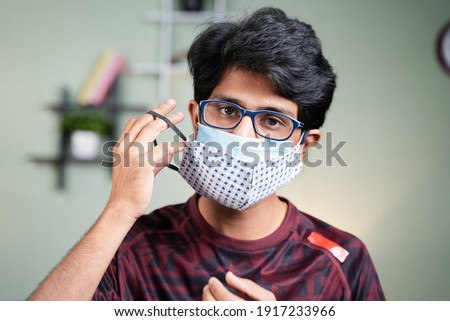 Portrait Young man wearing double or two face mask to protect from coronavirus or covid-19 outbreak - concept of safety, healthcare, medical and hygiene. Foto stock ©